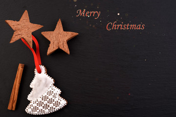 Christmas background with fir tree and decor. Gingerbread cookies on black stone background.
