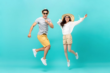 Energetic Asian couple in summer beach casual clothes jumping Wall mural