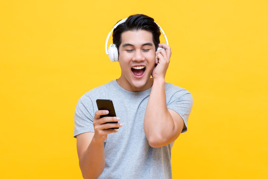 Happy young Asian man wearing wireless headphones listening to music from smartphone