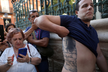 Camilo Esteban shows his tattoo of Spanish singer Camilo Sesto as he waits to pays his respects during his wake in Madrid