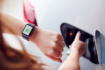 Man Charging Electric Vehicle With Cable Looking At App On Smart Watch