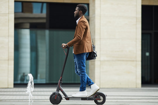 Side view full length of modern African-American businessman riding electric scooter while commuting to work in city, copy space
