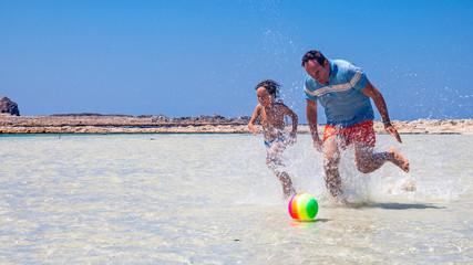 padre e figlio giocano sulla spiaggia di Balos a creta, Grecia