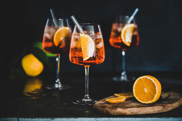 Papiers peints Bar Aperol Spritz aperitif with oranges and ice in glass with eco-friendly glass straw on concrete table, black background, selective focus. Summer refreshing drink concept