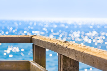 Lookout for Tranquility on Shiny Ocean / Wooden railing and wide view to glittering sea at sunny day (copy space)