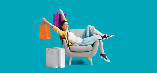 Cheerful shopaholic woman with shopping bags
