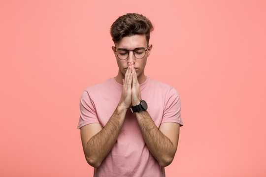 Young cool caucasian man holding hands in pray near mouth, feels confident.
