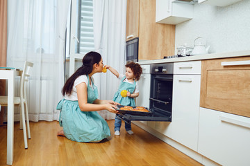 Mother and daughter cook pastries in the oven in the kitchen