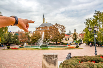 Male hand pointing at the blurred Banski Square with Banya Bashi Mosque, famous touristic place in Sofia downtown, Bulgaria