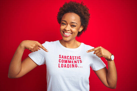 African american woman wearing sarcastic comments t-shirt over red isolated background looking confident with smile on face, pointing oneself with fingers proud and happy.