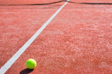 Tennis ball on red court during sunny day
