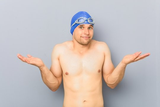 Young professional swimmer man doubting and shrugging shoulders in questioning gesture.