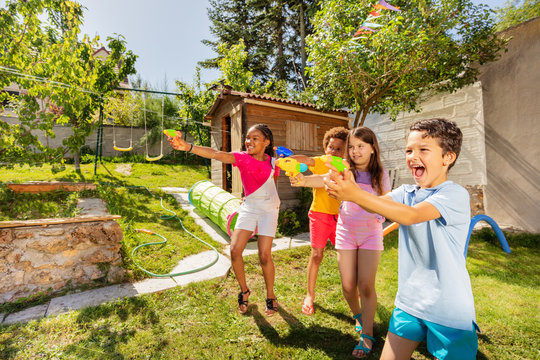 Kids play water gun fight in a team with friends