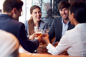 Group Of Business Colleagues Making A Toast As They Meet For Drinks And Socialize In Bar After Work