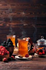 Spoed Foto op Canvas Thee Freshly brewed fruit and herbal tea in kettle and two cups, dark mood.