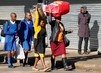 Parents carry luggage on their heads as they accompany their children back to school in Harare
