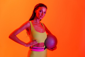 Photo of pretty brunette woman wearing formfitting sportswear holding gymnastic ball while doing workout