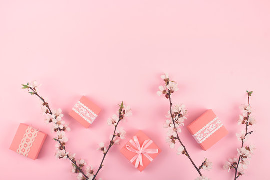 Flat lay with pink gift boxes and blooming cherry sakura flowers on pastel background. Birthday gift girl pink background with copy space