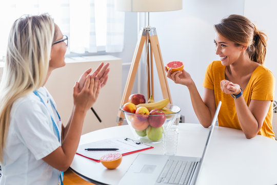 Professional nutritionist meeting a patient in the office and healthy fruits with tape measure, healthy eating and diet concept
