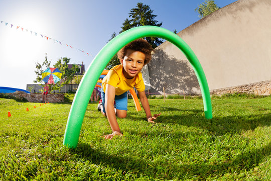 Kids crawl under course of barriers on his fours