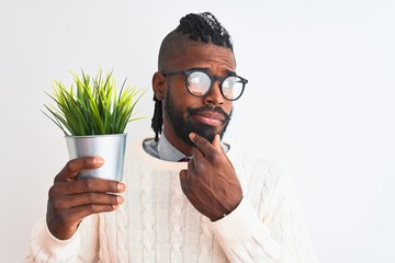 African american man with braids holding plant pot over isolated white background serious face thinking about question, very confused idea
