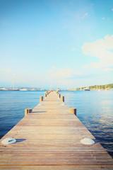 Paysage marin au bout d'un ponton en bois dans la baie des canebiers à Saint Tropez, Vars, Provence, France, eau bleue turquoise et colline à la végétation verte avec des voiliers