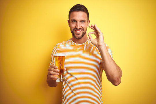 Young handsome man drinking a pint glass of beer over isolated yellow background doing ok sign with fingers, excellent symbol