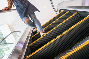 Young girl  wearing torn jeans walking down an escalator with light bright background and dark steps with yellow strips in foreground.
