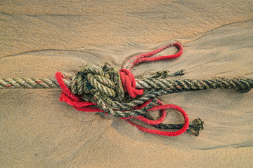 Red knotted ships rope 8. Creative red knotted ships rope lying on a sandy beach leading out to sea on the shoreline as the tide comes in.