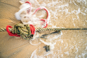 Red knotted ships rope 2. Creative red knotted ships rope lying on a sandy beach leading out to sea on the shoreline as the tide comes in.