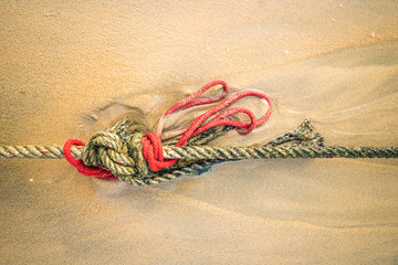 Red knotted ships rope 1, Creative red knotted ships rope lying on a sandy beach leading out to sea on the shoreline as the tide comes in.
