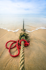 Red knotted ships rope 3. Creative red knotted ships rope lying on a sandy beach leading out to sea on the shoreline as the tide comes in.