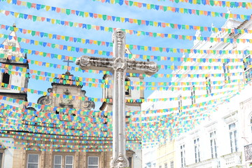 Cross and church decorated with colorful pennants, Salvador de Bahia