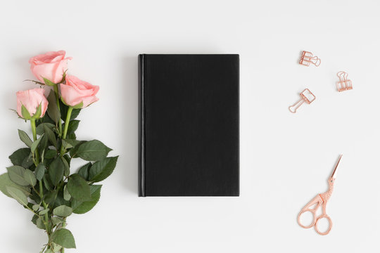 Top view of a black book mockup with a bouquet of pink roses and workspace accessories on a white table.
