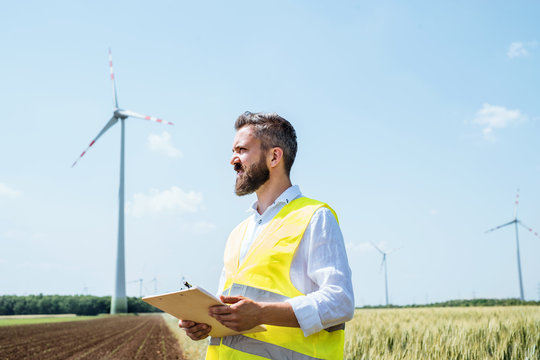 An engineer standing on a field on wind farm, making notes.