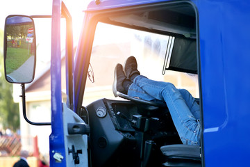 the truck driver rests in the cab of the car with his feet on the steering wheel