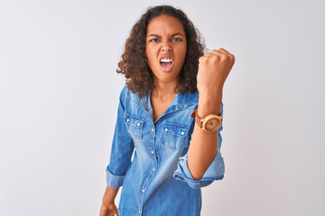 Young brazilian woman wearing denim shirt standing over isolated white background angry and mad raising fist frustrated and furious while shouting with anger. Rage and aggressive concept.