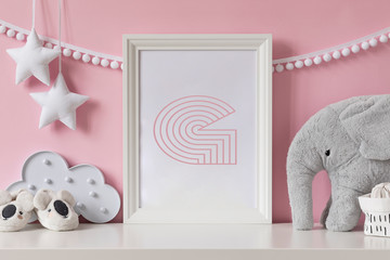 Modern scandinavian newborn baby room with mock up poster frame, plush elephant, cloud, shoes and children accessories. Cozy interior with pink walls. Haniging cotton garland and stars. Template