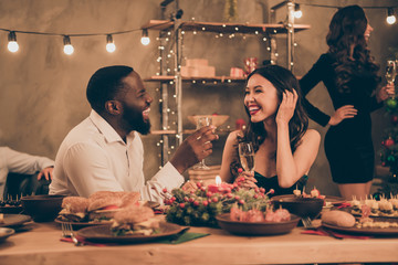 Profile side photo of cheerful couple of mixed-race man and chinese woman give toast hold champagne speak enjoy christmas party x-mas night in house with table full of newyear dinner feat indoors