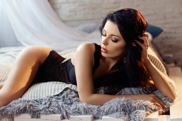 Sexy brunette woman in black lingerie at home on the bed. Perfect figure, beautiful body on the girl. Smooth clean skin and long strong hair. The girl in the light of the yellow lamp