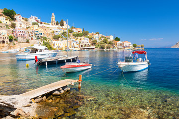 Boats and colorful houses in bay of Symi, symi island, Greece