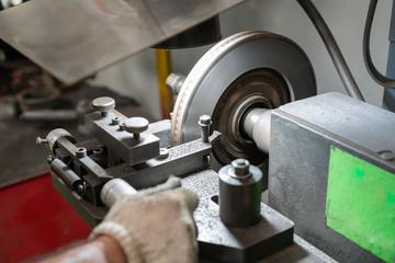 Mechanic man repairing brake use lathe tool polishing disc brakes of cars working automatic. - rebuild disc brake surface.