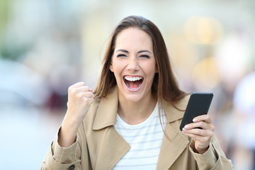 Excited woman holding phone looking at camera