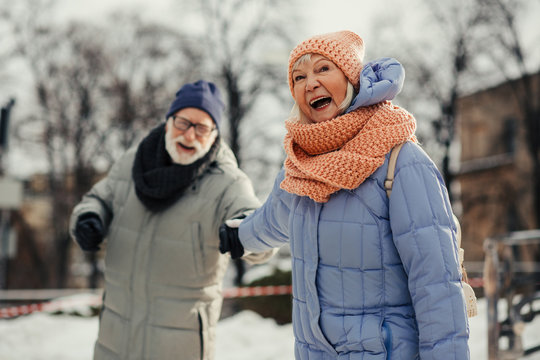 Excited aged woman pulling hand of her husband and smiling