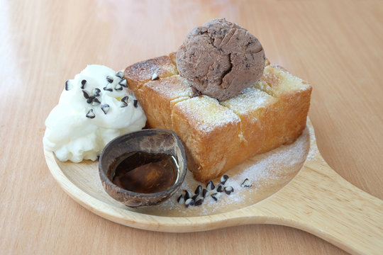 Honey toast and ice cream on a wooden plate