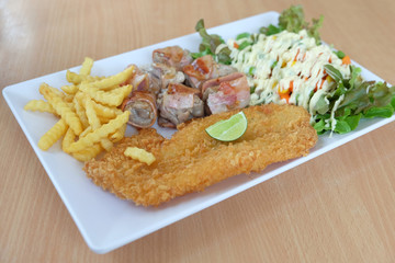 Fried fish, bacon roll, french fries, vegetable salad in white plate