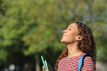 Happy mixed race student breathing fresh air in a park Wall mural