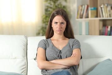 Annoyed woman looking at camera at home