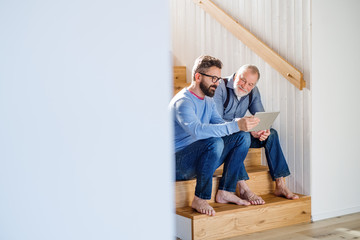 An adult son and senior father with tablet sitting on stairs indoors at home. Wall mural