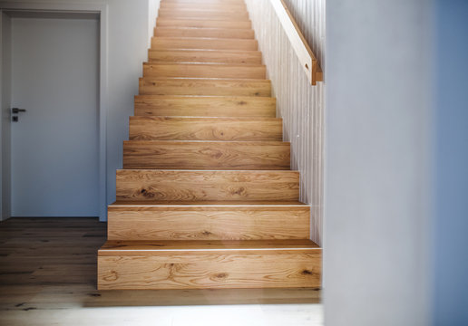 A wooden staircase and white wall in an interior of a house.